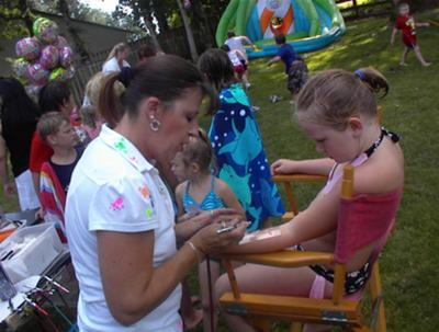 Airbrushing tattoos at a birthday party.